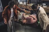 Fotografia amici multietnici versando birra nellimbuto e bevente delluomo mentre sdraiato sul tavolo