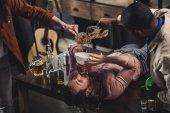 Fotografia ritagliata colpo di amici birra nellimbuto e bevente delluomo mentre sdraiato sul tavolo di versamento