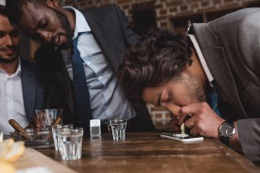 cropped shot of multiethnic businessmen looking at friend taking cocaine