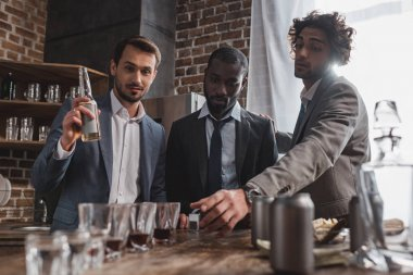 young multiethnic friends in suits drinking alcohol beverages together