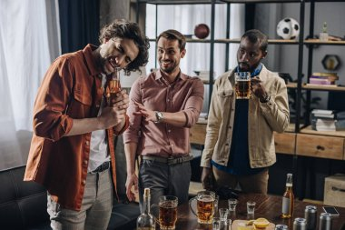 young multiethnic men looking at friend opening beer bottle with teeth