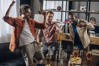cheerful multiethnic men friends having fun and looking at tower from bottles and glasses while partying indoors