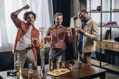 happy male friends cheering and drinking beer together