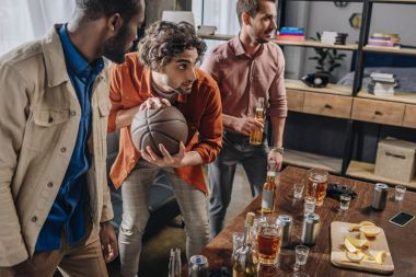 young multiethnic men playing with basketball ball and drinking beer together