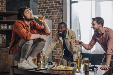 smiling multiethnic men looking at friend drinking beer while crouching on table