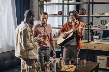 happy multiethnic male friends drinking beer and playing guitar together