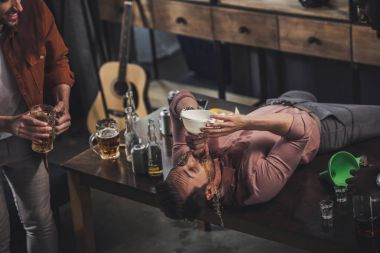 young man lying on table and drinking beer from funnel while friends looking at him