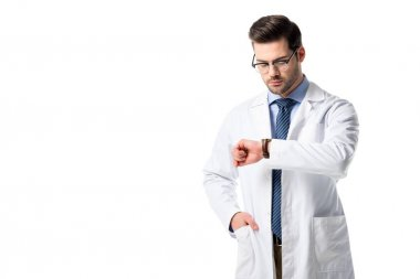 Male doctor wearing white coat checking his watch isolated on white
