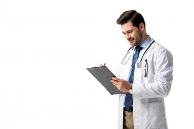Doctor wearing white coat with stethoscope and writing diagnosis in clipboard isolated on white
