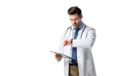 Doctor with clipboard wearing white coat with stethoscope and checking his watch isolated on white