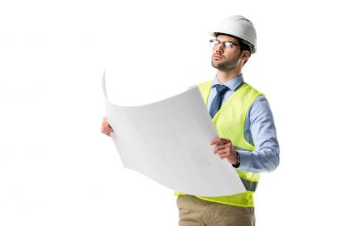 Confident architect in glasses wearing reflective vest and hardhat looking at blueprint isolated on white