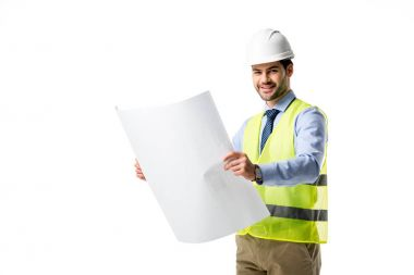 Smiling builder in reflective vest and hardhat looking at blueprint isolated on white