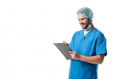 Cheerful surgeon  wearing blue uniform and holding clipboard isolated on white