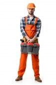 Photo Confident handyman in orange overall and hard hat holding tool box isolated on white