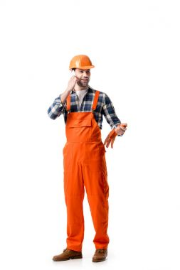 Young repairman in orange overall and hard hat talking on the phone isolated on white stock vector