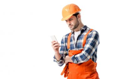 workman in orange overall and hard hat using smartphone isolated on white