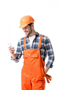 Smiling handyman in orange overall and helmet using smartphone isolated on white