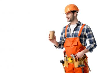 Smiling builder in orange overall and tool belt drinking coffee isolated on white