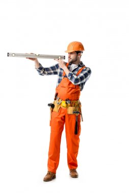 workman in orange overall and hard hat checking spirit level isolated on white