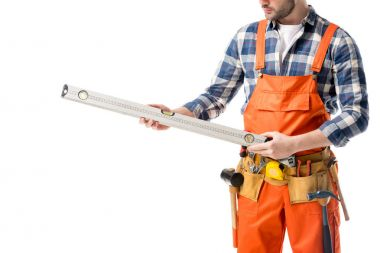 Close-up view of spirit level in hands of workman in orange overall isolated on white