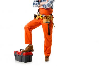 Cropped view of workman in orange overall leaning on tool box isolated on white