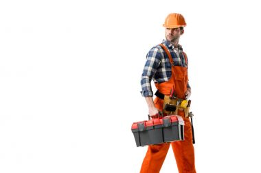 Young builder in orange overall and hard hat carrying tool box isolated on white