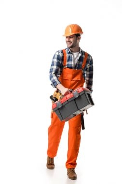 Smiling builder in orange overall and helmet carrying tool box isolated on white