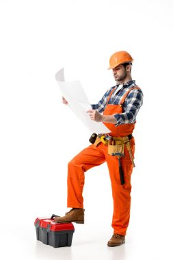 Builder in orange overall and helmet looking at blueprint while leaning on tool box isolated on white
