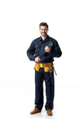 Confident handyman wearing uniform with tool belt and holding wrench isolated on white