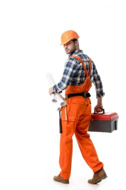 Young builder in orange overall and helmet carrying tool box and blueprint isolated on white
