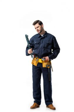 Young handyman wearing uniform with tool belt and looking at wrench isolated on white