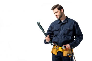 Bearded sanitary engineer wearing uniform with tool belt and looking at wrench isolated on white
