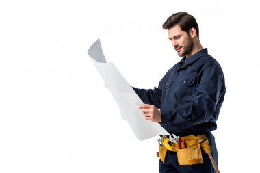 side view of plumber in uniform looking at blueprint in hands isolated on white