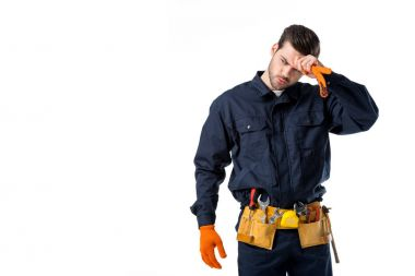 portrait of tired plumber in uniform and protective gloves looking away isolated on white