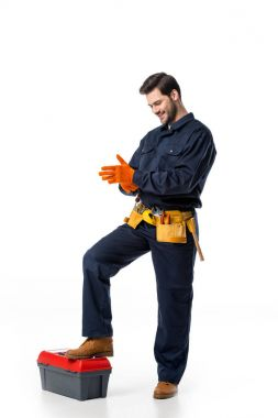 smiling plumber in uniform wearing protective gloves isolated on white