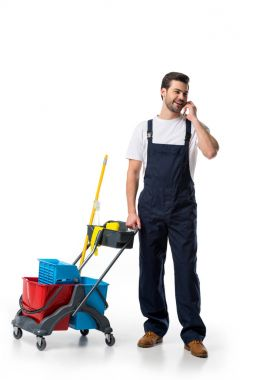 cleaner in uniform with cart talking on smartphone isolated on white