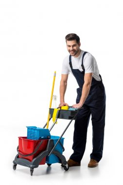 smiling cleaner in uniform with cart isolated on white