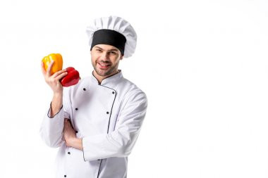 smiling chef in uniform with fresh bell peppers in hand isolated on white