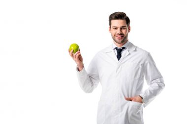 portrait of smiling nutritionist in white coat with fresh apple in hand isolated on white