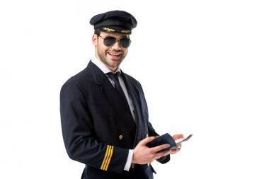 Smiling pilot in uniform and sunglasses wit passport and ticket isolated on white stock vector