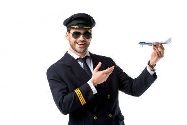 portrait of smiling bearded pilot in uniform pointing at toy plane in hand isolated on white