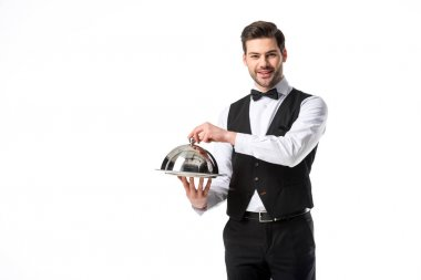 portrait of handsome smiling waiter in suit vest with serving tray isolated on white