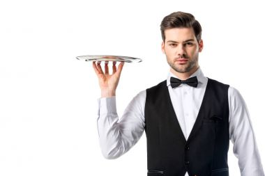 portrait of handsome waiter in suit vest with empty serving tray isolated on white