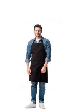young smiling waiter in apron looking at camera isolated on white