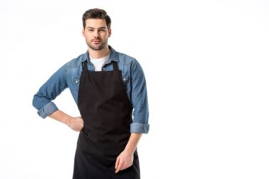 portrait of young bearded waiter in apron standing akimbo isolated on white
