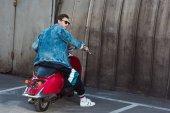 mladý muž v elegantní džínové bundy s skůtru na parkování