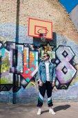 pohledný mladý muž v vintage oblečením před cihlovou zeď s graffiti a basketbalový kroužek