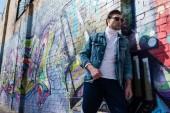 elegantní mladý muž v vintage oblečením, opíraje se o cihlovou zeď s graffiti