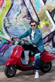 Photo attractive young man on vintage red scooter in front of brick wall with graffiti