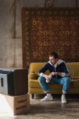 Fotografie handsome young man in vintage clothes with bottle of milk watching tv